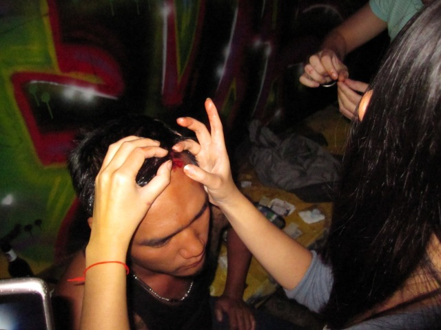 One of the girls at the bar attempting to suture the guy's gaping (~1 inch) head wound